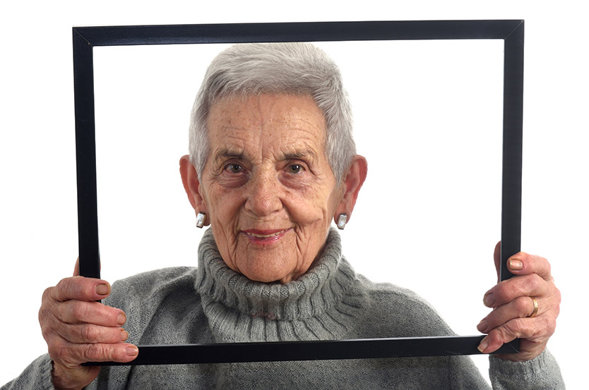senior retired woman looks through frame