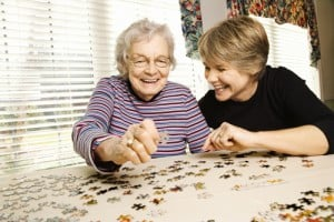woman completing puzzle with memory care resident