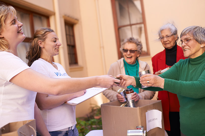 women from senior living communities donate food