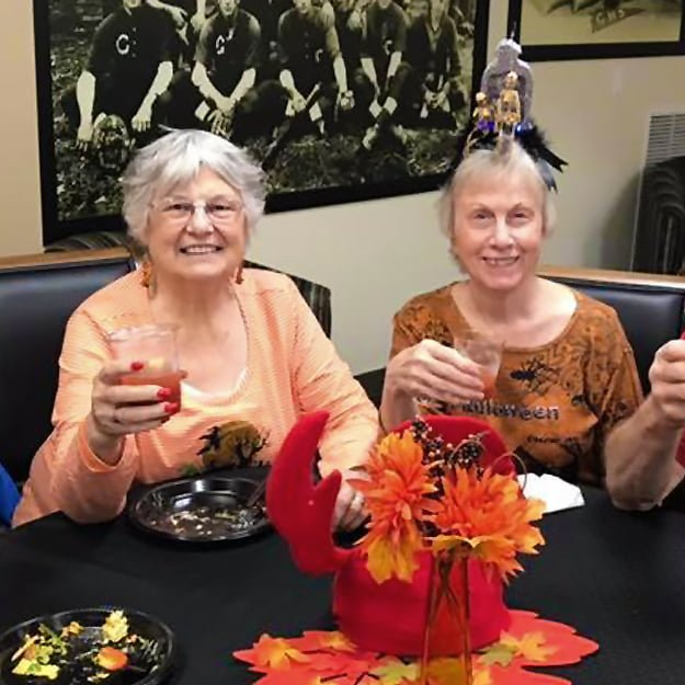 Two senior ladies toasting in Halloween Costumes