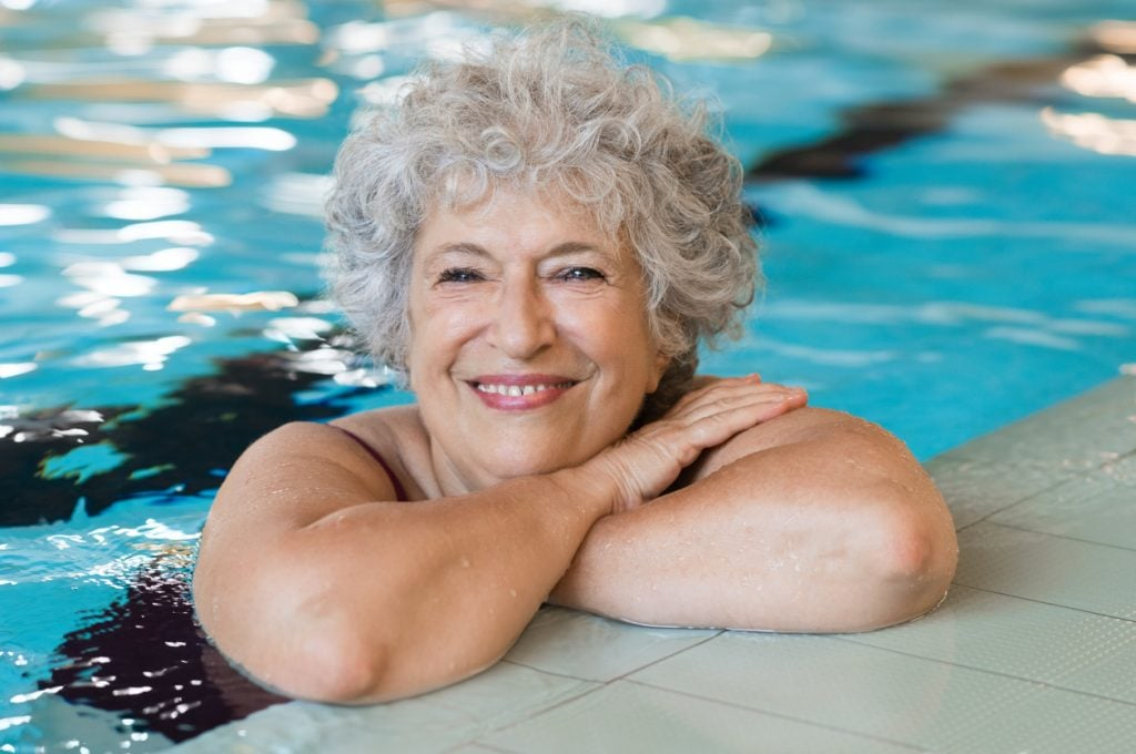 Portrait of elderly woman against the edge of a swimming poo