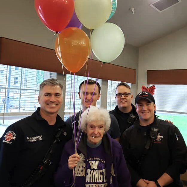 Cops and senior hold balloons in Puyallup Washington senior living community in assisted living