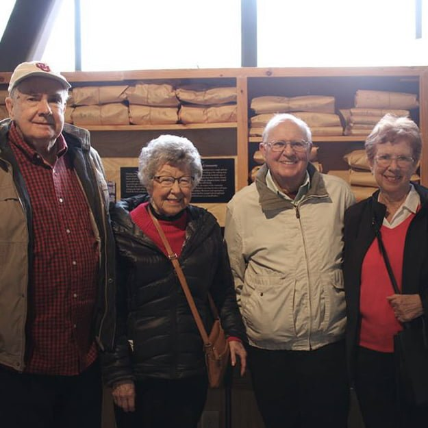 4 seniors by wall at Bonaventure of Tigard in Oregon smile in their retired living life