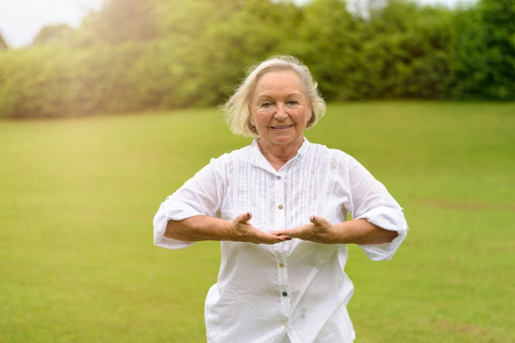 Senior woman exercising her lungs in her assisted living community