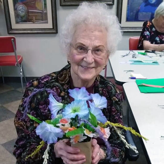 Assisted living and memory care senior enjoys her retirement and flowers