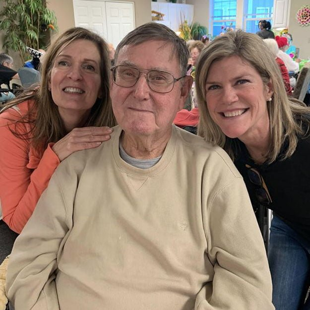 Memory care senior is embraced by daughters in his memory care for assisted living retirement seniors