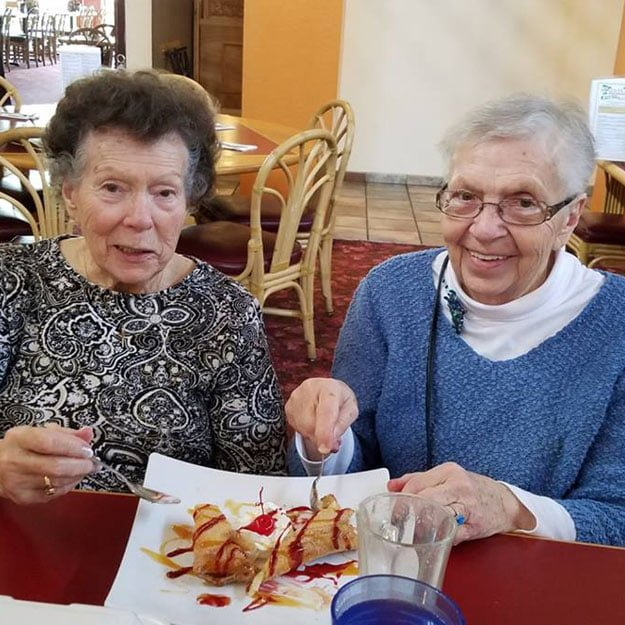 Women at an assisted living senior community enjoy the food