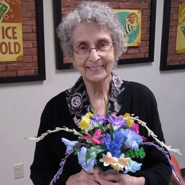 Assisted living senior loves flowers and independent living in her retirement