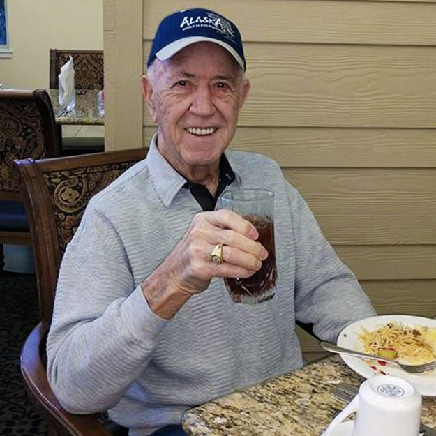 Happy man drinks in his independent living community for seniors with assisted living needs like memory care