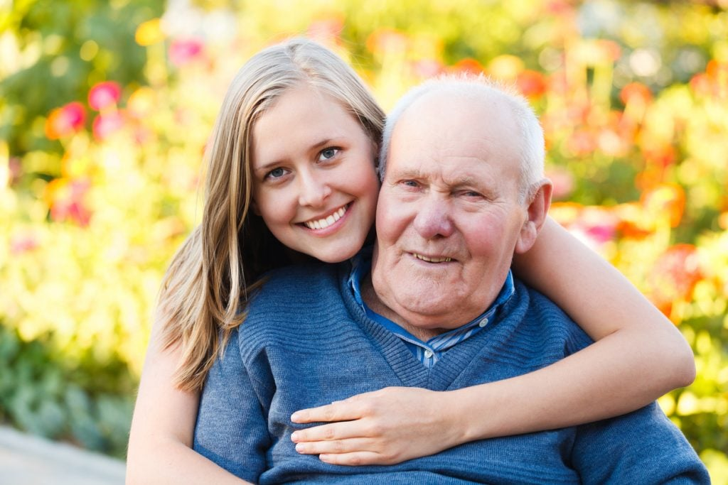 A family caregiver with her senior family member in his independent living community for those that need assisted living or memory care in their retirement