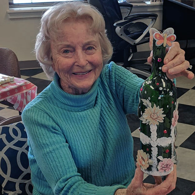 Independent living woman does art in her memory care and assisted living community