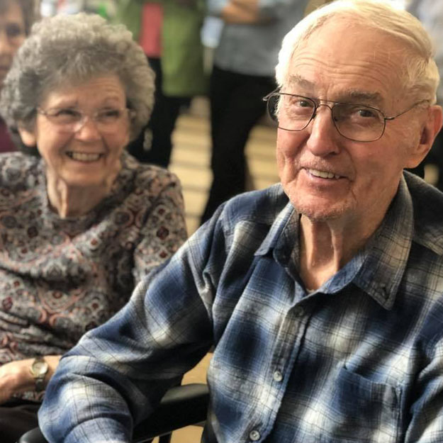 Memory care couple smiles in their independent living and assisted living community