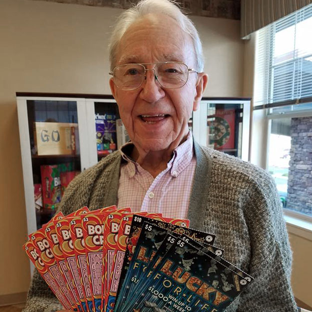 Man in senior living community holds lottery tickets for seniors assisted and retirement independent