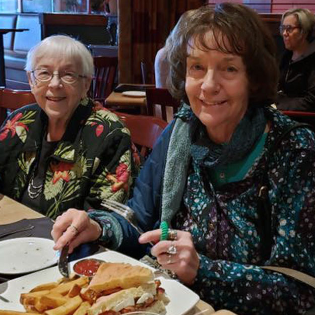 Memory care seniors eat food in their retirement living community for independent living