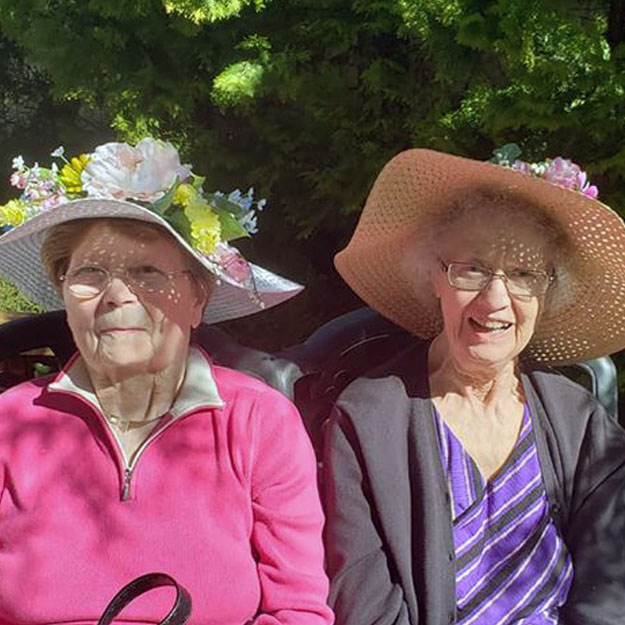 Assisted living women wear hats in memory care or independent living community