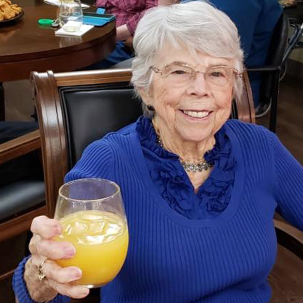 Assisted living lady drinks to her retirement and memory care community