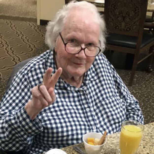 Assisted living senior gives peace sign in her independent living community