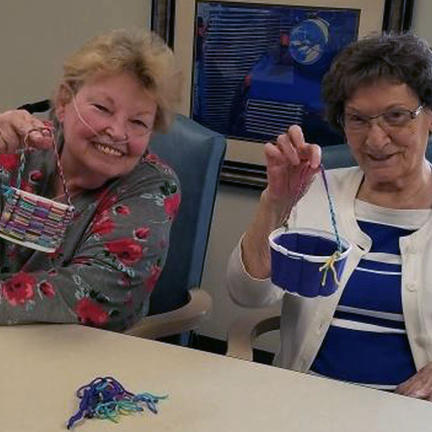 Memory care resident seniors making things in their retirement living community