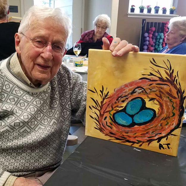 Memory care senior enjoying painting in his assisted living retirement community