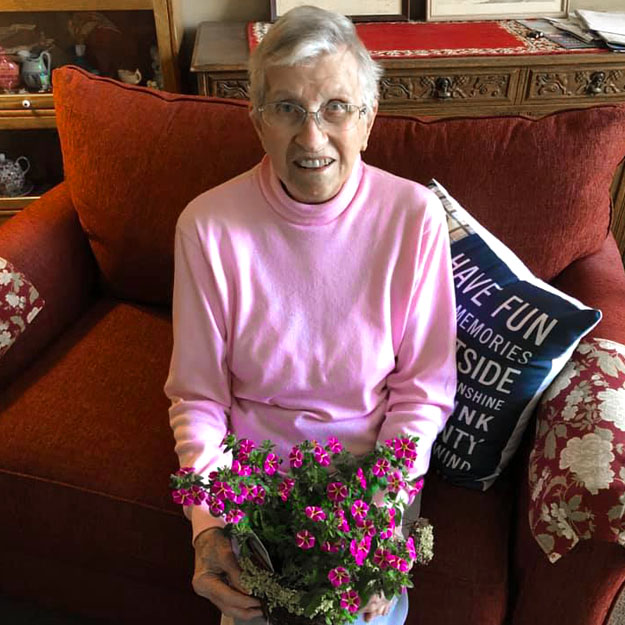 Woman in Vancouver assisted living holds plant for memory care