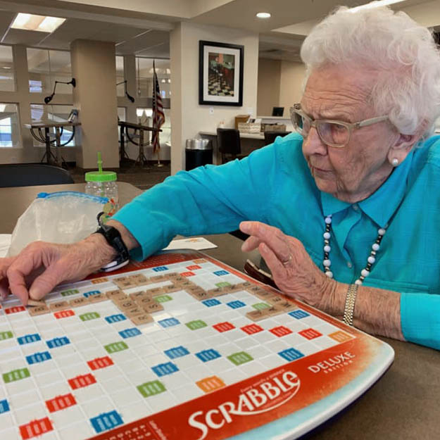 Senior in memory care plays games in her retirement living community