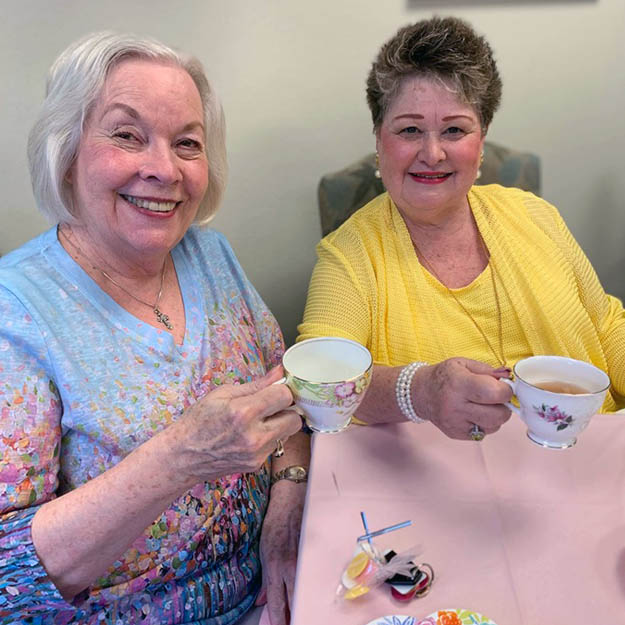 Memory care women smile at the camera in their independent living community and assisted living