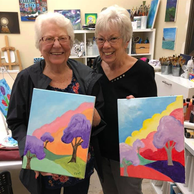 Senior women are proud of paintings in memory care living community