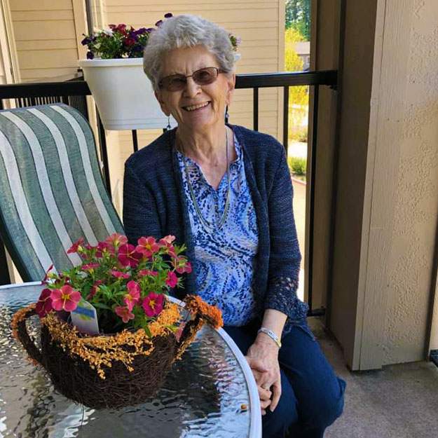 Senior woman poses in front of retirement living community plants