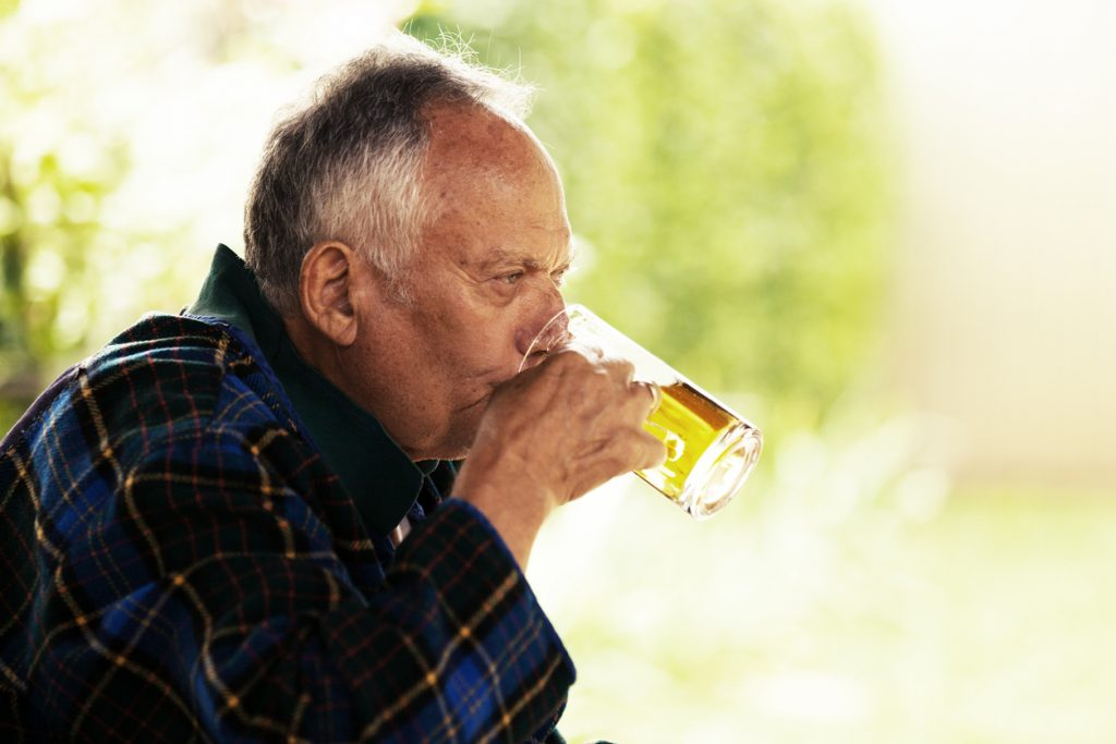 Senior drinking alcohol in his retirement living community for assisted living and memory care