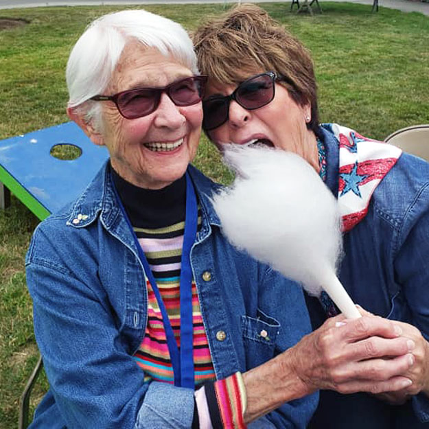 Two senior women enjoy cotton candy and laughing in assisted living community