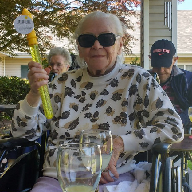 Happy memory care senior has fun in her retirement living community