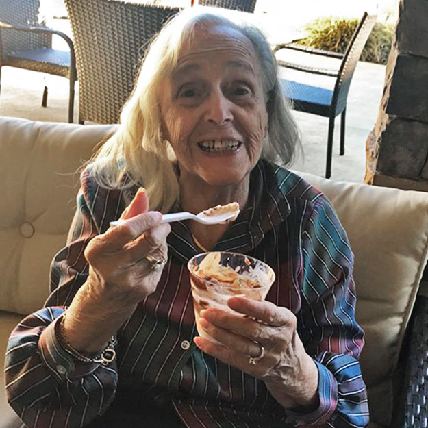 Senior woman enjoys ice cream in her assisted living community for memory care seniors