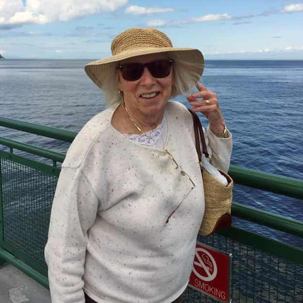 Senior woman in hat near ocean because of retirement living community and assisted living memory care