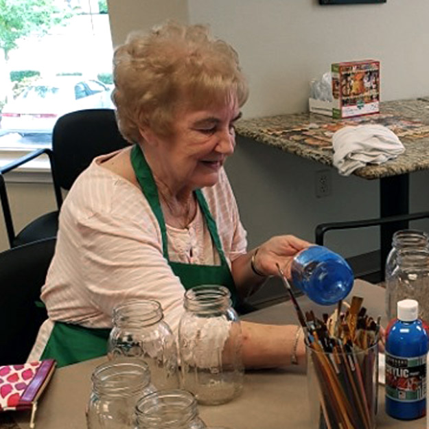 Senior woman does crafts in her assisted living community for memory care seniors