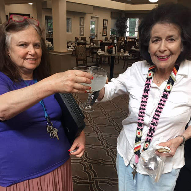 Two senior women cheers to great retirement living community for memory care and assisted living seniors