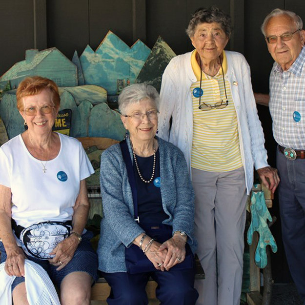 Group of assisted living seniors pose in memory care community for retirement