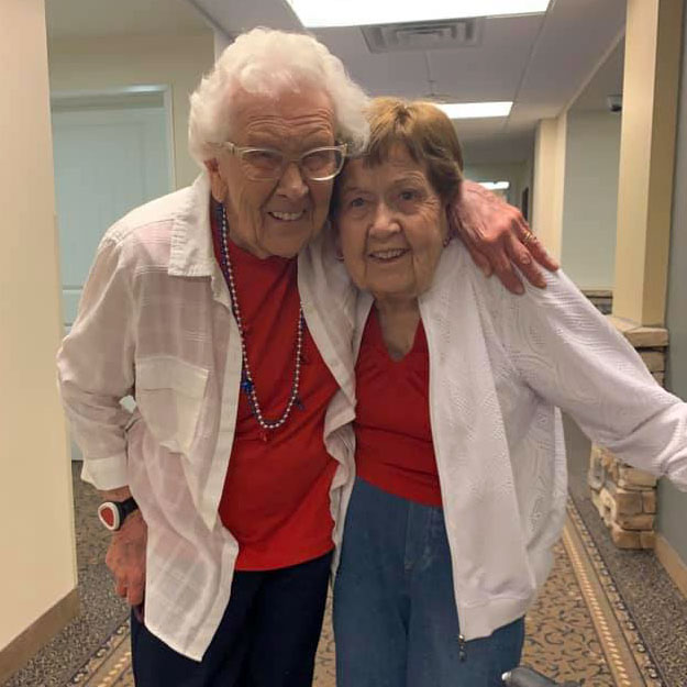 Two senior woman embrace and smile while living in memory care