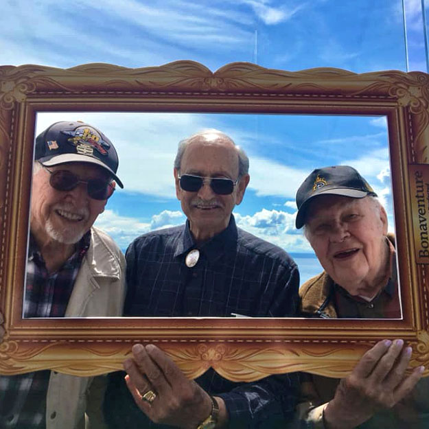 Three senior men pose for photo in independent living community