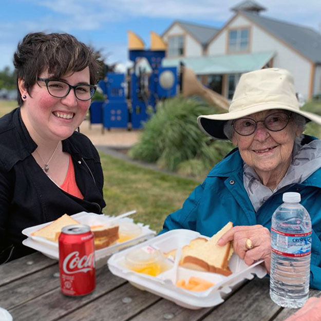 Memory care senior and caregiver enjoy lunch in their assisted living community