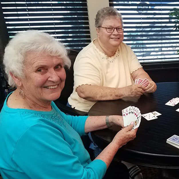 Seniors play cards in retirement living community