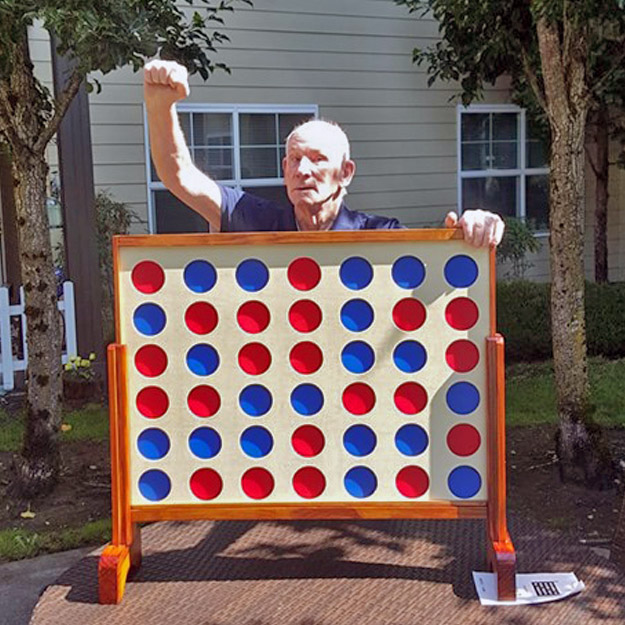Senior man and giant game have fun in memory care living community and assisted retirement