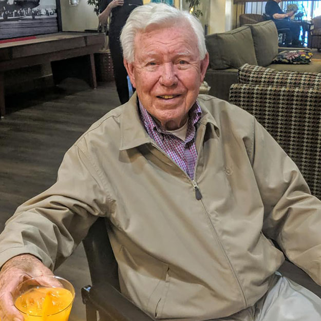 Senior man enjoys a drink in his memory care community