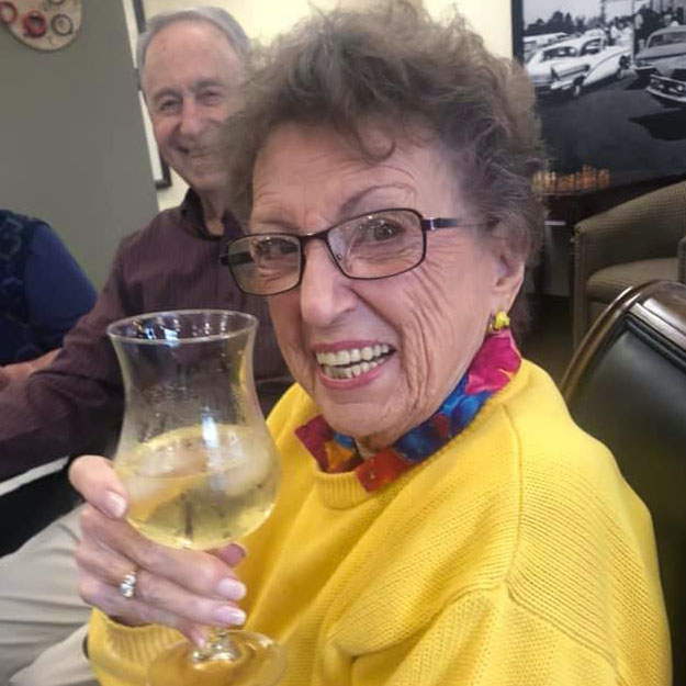 Senior woman has wine in assisted living