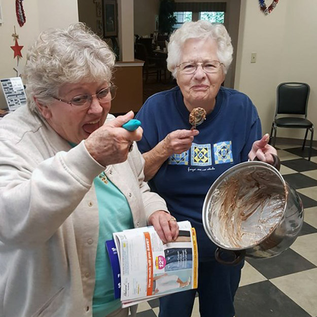 Two seniors eat ice cream in their assisted living community