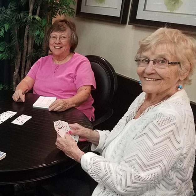 Assisted living senior women play cards in memory care