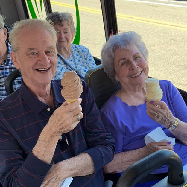 Two happy seniors enjoy ice cream and retirement living community
