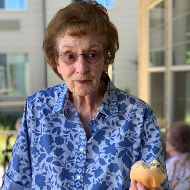 Senior woman stunned at how much she enjoys retirement living community and assisted memory care