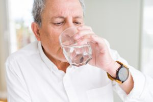 Senior man drinking water in his retirement assisted living and memory care community