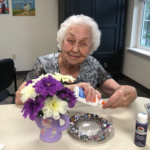 Memory care senior makes flowers in her independent living community