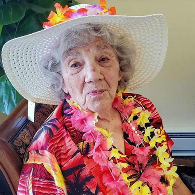 Senior woman in hat has fun in retirement living community for memory care seniors